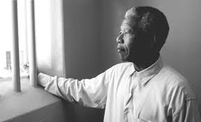 Nelson Mandela re-visiting his cell on Robben Island after his election as President of South Africa.