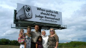 Michael Bell Sr. (center) and his family stand near one of the billboards they bought in a campaign to bring awareness to internal police investigations. Bell's son was shot and killed by police in Kenosha, Wis.