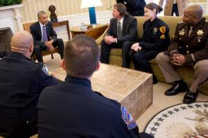 (Jacquelyn Martin | The Associated Press) President Barack Obama talks with Officer Allan Gerking of the Puyallup, Wash., Tribal Police Departmen, center, Sgt. Charli Goodman of the Salt Lake City Police Department and Cpl. Dorrell Savoy of the Charles County, Md., Sheriff's Office, as he meets Tuesday with law enforcement officials from across the country in the Oval Office of the White House. In the foreground are Officer Erik Oliver of the Richmond, Calif., Police Department, left, and Officer Matthew Thomas of the Indianapolis Metropolitan Police Department.